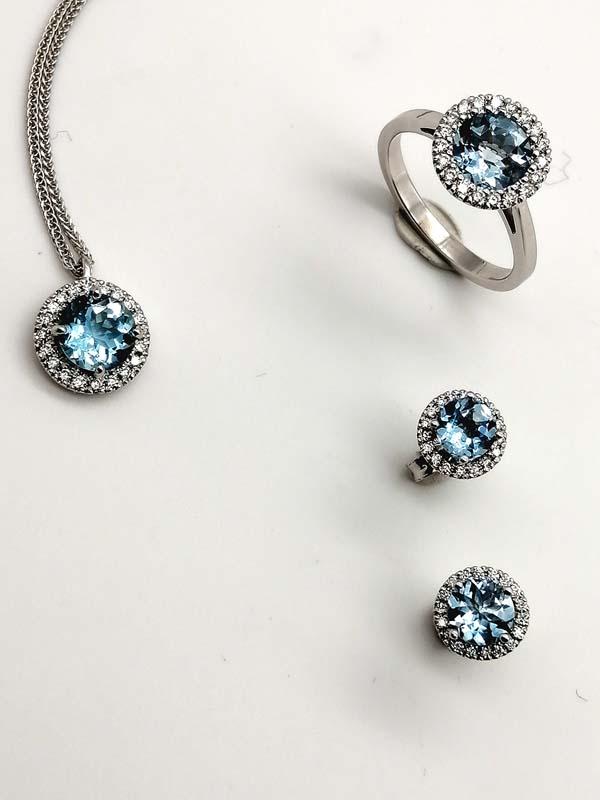 Anello, orecchini e ciondolo in oro bianco con acquamarina e contorno di diamanti